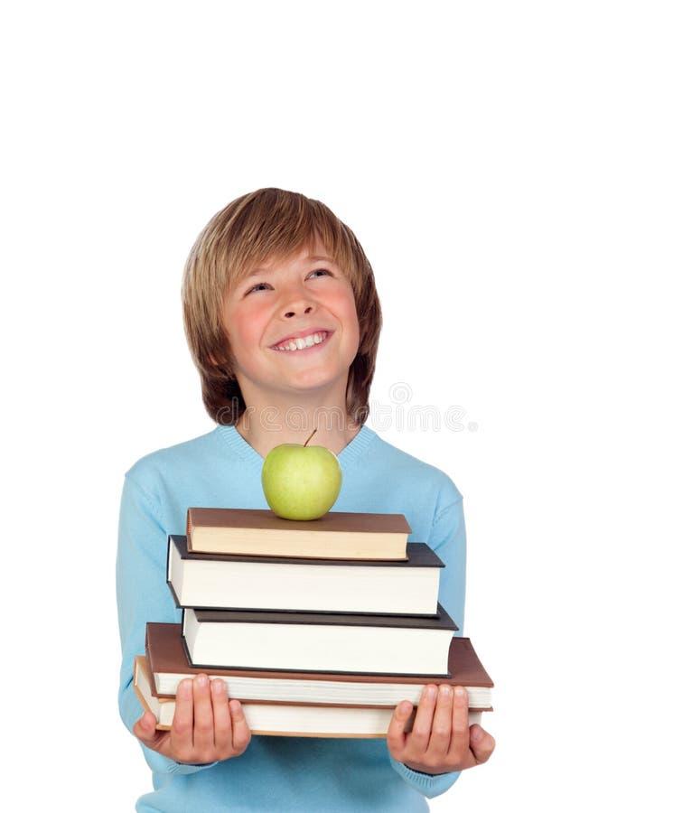Menino do Preteen com muitos livros que olham acima imagem de stock royalty free
