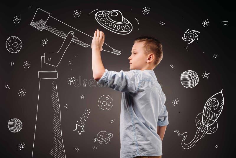 menino do preteen que finge ser um astrônomo com telescópio e o UFO tirados, planetas, nave espacial imagem de stock