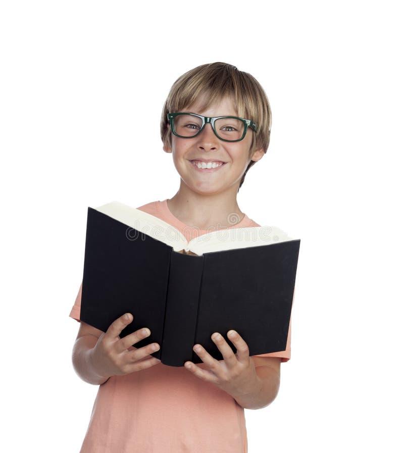 Menino do Preteen que lê um livro com vidros imagem de stock