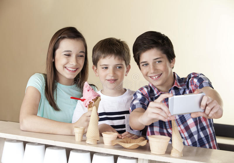 Menino do Preteen que toma Selfie com os irmãos através do telefone esperto foto de stock
