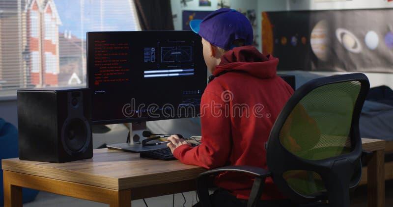 Menino do programador que codifica em seu computador imagens de stock