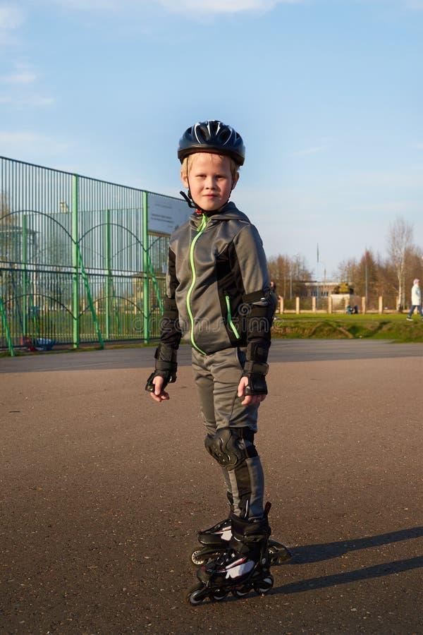Menino do retrato em patins de rolo no crescimento completo foto de stock royalty free