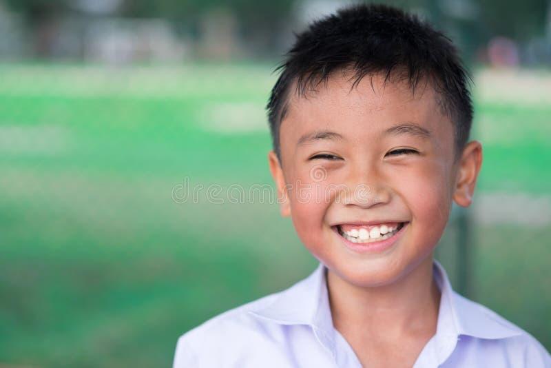 Menino do retrato A que sorri e feliz no fundo da natureza foto de stock