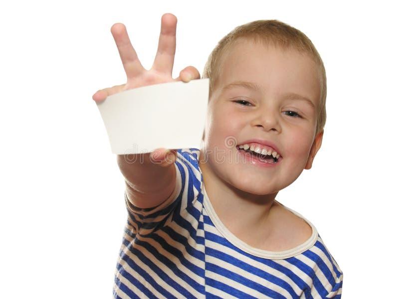 Menino do sorriso com o cartão para o texto imagem de stock