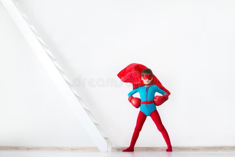 Menino do super-herói em luvas de encaixotamento vermelhas e um cabo no vento foto de stock