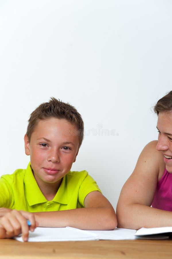 Menino do Tween que faz lições dos trabalhos de casa com sua mãe imagens de stock