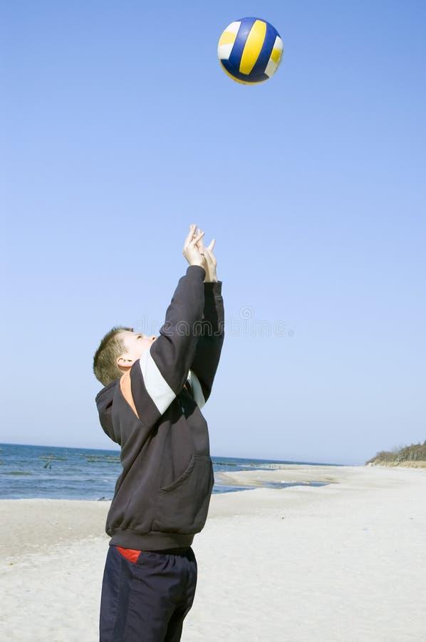 Menino do voleibol na praia. fotografia de stock