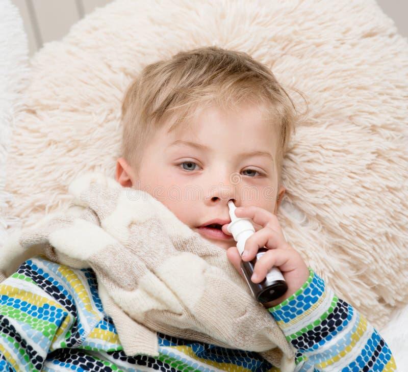 Menino doente com a gripe em casa que usa o pulverizador de nariz fotografia de stock royalty free