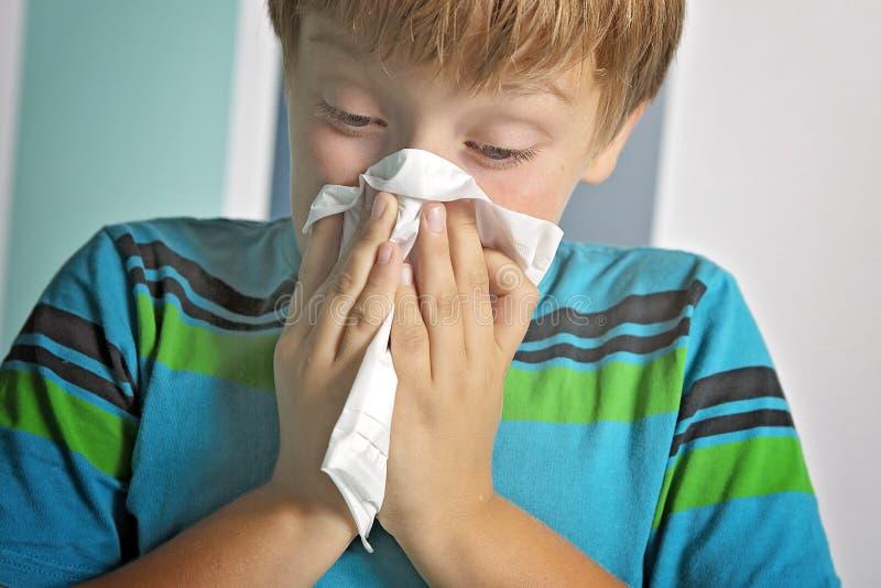 Menino doente com o nariz de sopro da gripe em casa foto de stock royalty free