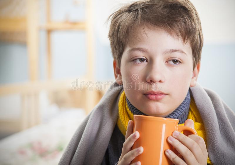 Menino doente com um copo do ch? em casa foto de stock