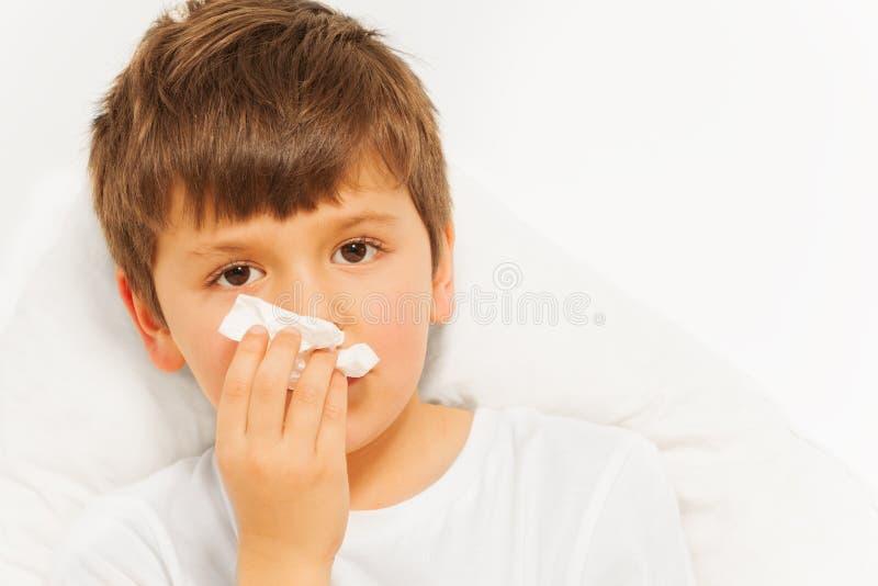 Menino doente da criança com frio mau usando os guardanapo de papel imagens de stock