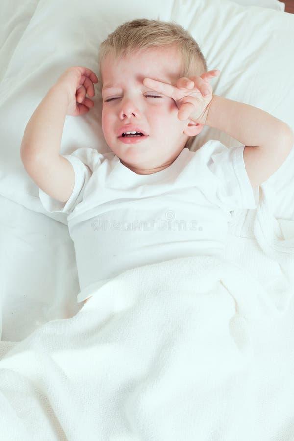 Menino doente da criança que grita na cama fotos de stock