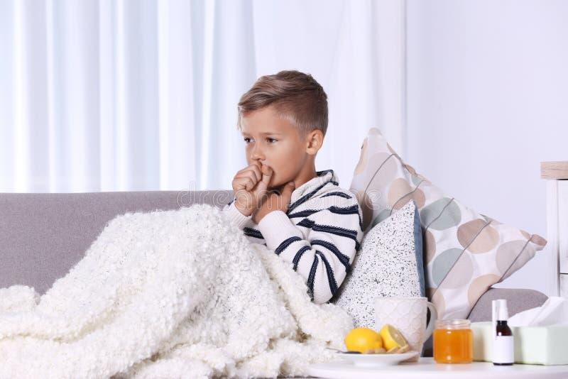 Menino doente que sofre da tosse no sofá imagens de stock