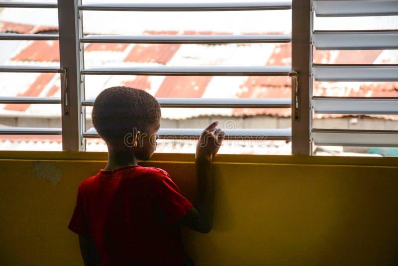 Menino dominiquense novo que olha para fora a janela fotos de stock