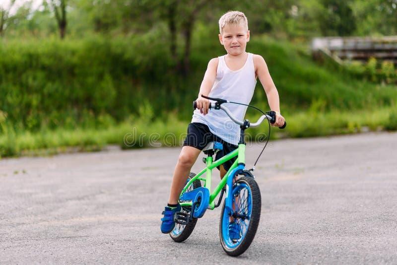Menino dos esportes de sete anos em um t-shirt branco que monta uma bicicleta de duas rodas no pavimento no verão imagem de stock royalty free