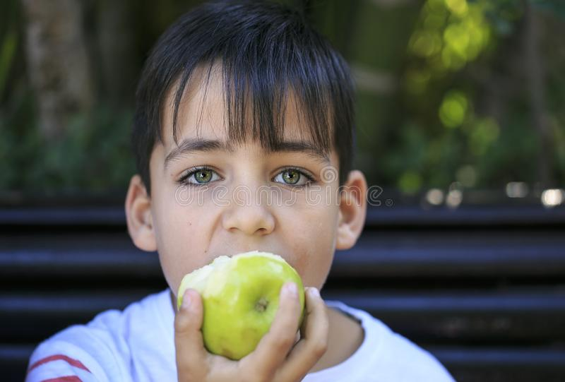 Menino dos olhos verdes que come uma maçã imagens de stock royalty free