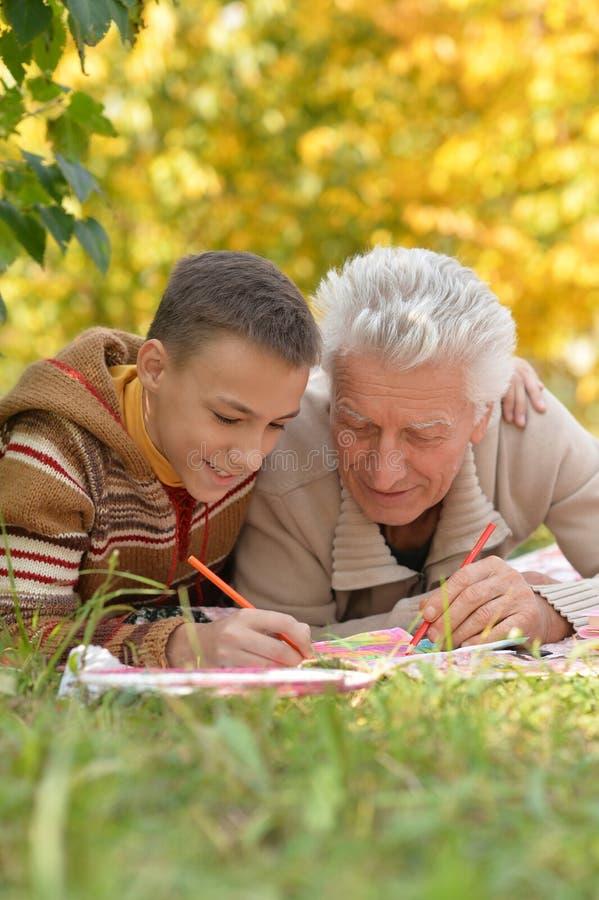 Menino e avô que fazem trabalhos de casa fotografia de stock