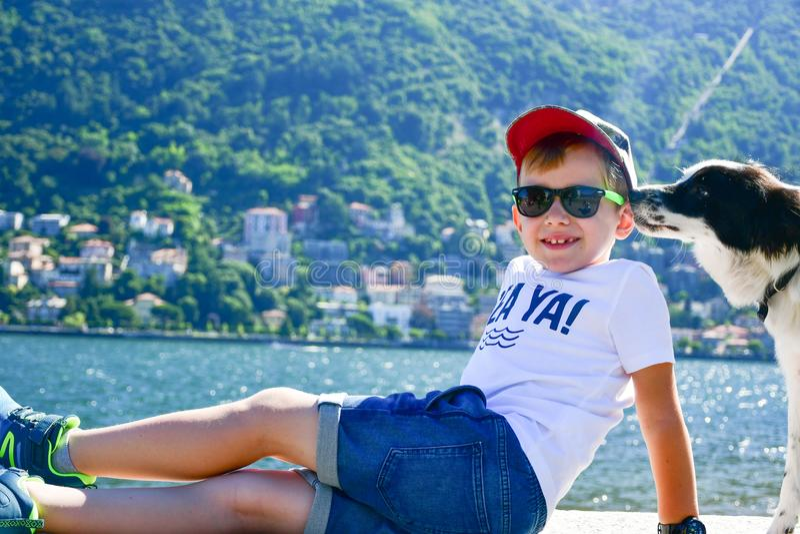 menino e cão felizes da forma no lago Como, Itália imagem de stock royalty free