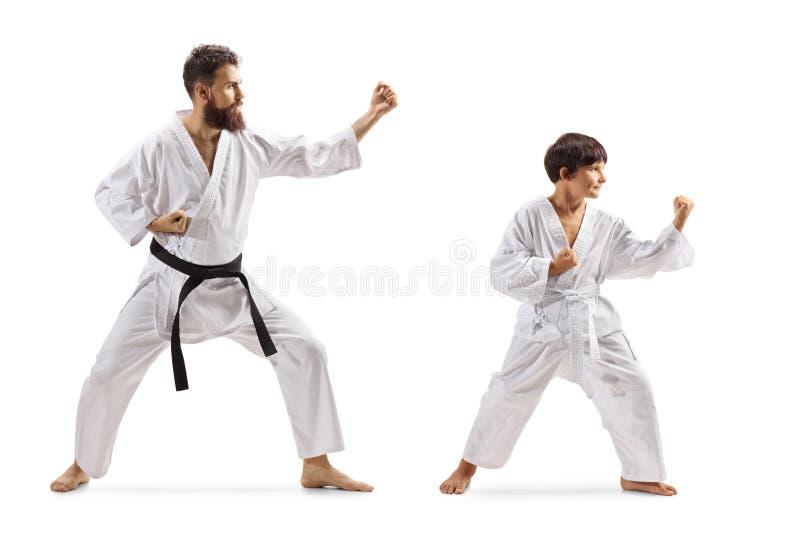 Menino e homem nos quimonos que praticam o karaté fotos de stock