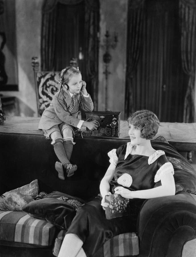 Menino e mãe com rádio (todas as pessoas descritas não são umas vivas mais longo e nenhuma propriedade existe Garantias do fornec imagens de stock royalty free