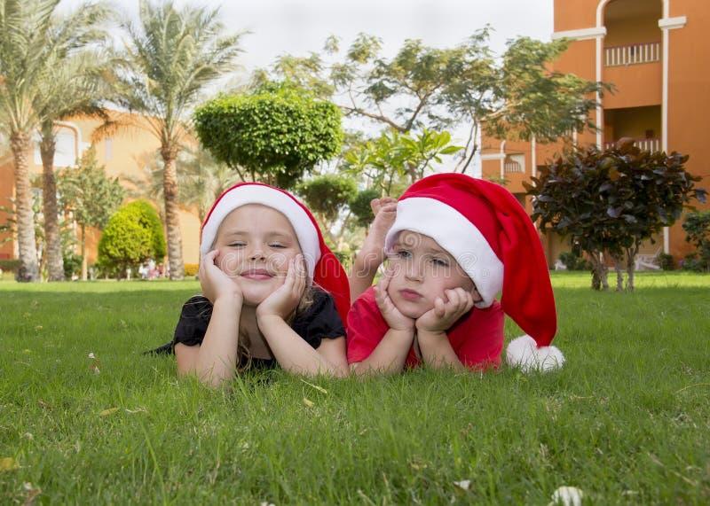 Menino e menina bonitos em chapéus de Santa imagem de stock