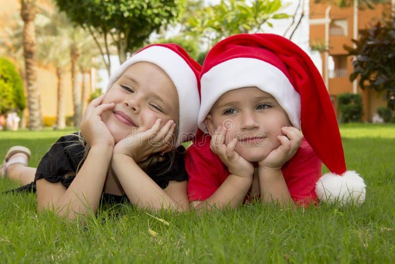 Menino e menina bonitos em chapéus de Santa fotografia de stock royalty free
