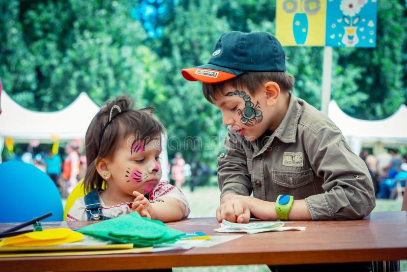 Menino e menina bonitos e engraçados com pinturas da cara no festival da família da caridade imagens de stock