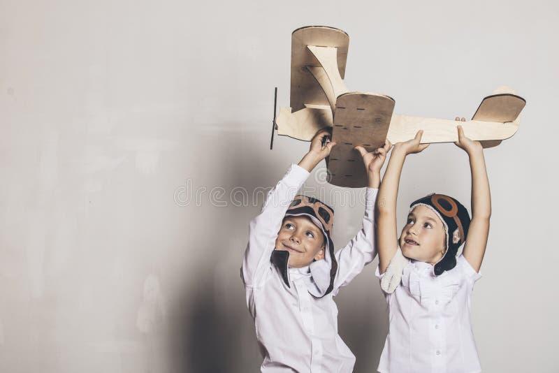 Menino e menina com o avião modelo de madeira e um tampão com desig do tampão fotografia de stock royalty free