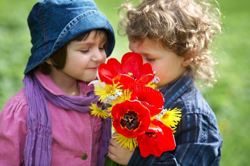 Menino e menina com o ramalhete das flores imagem de stock royalty free