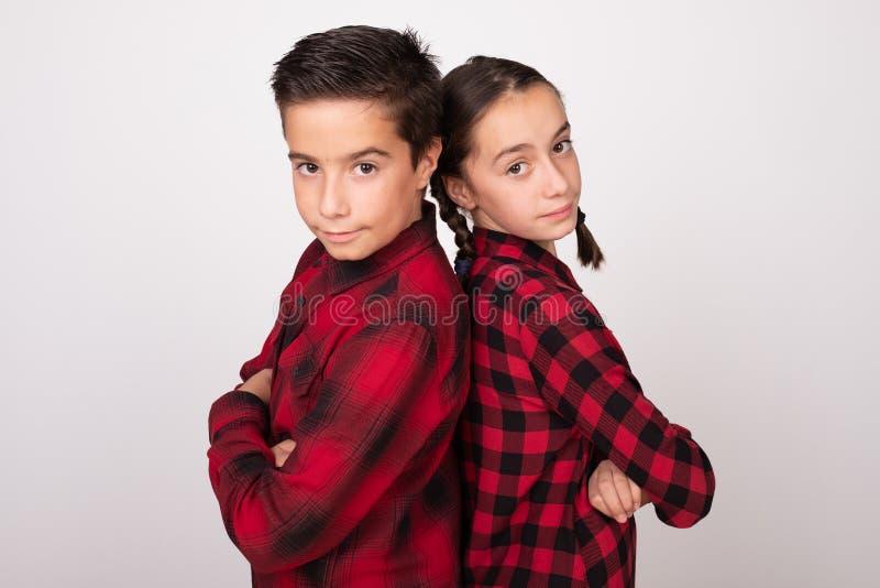 Menino e menina com os braços cruzados que levantam de volta à parte traseira com olhar de desafio fotos de stock royalty free