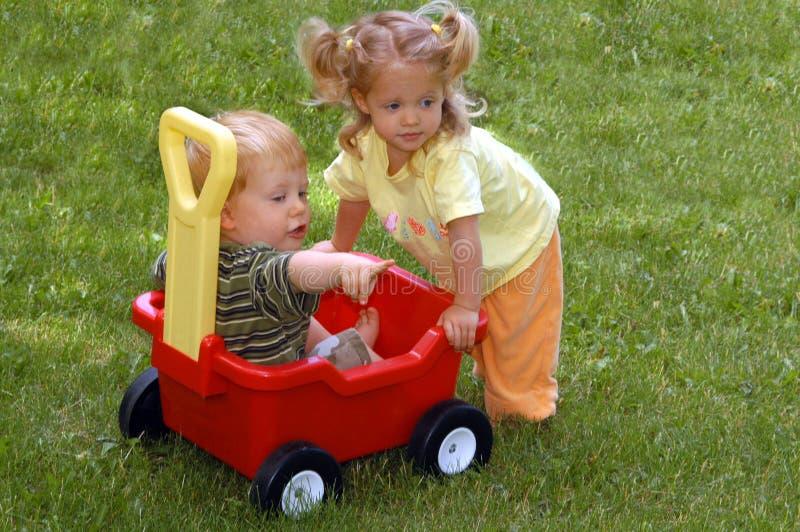 Menino e menina com vagão foto de stock royalty free