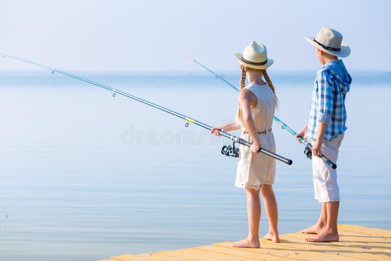 Menino e menina com varas de pesca fotos de stock