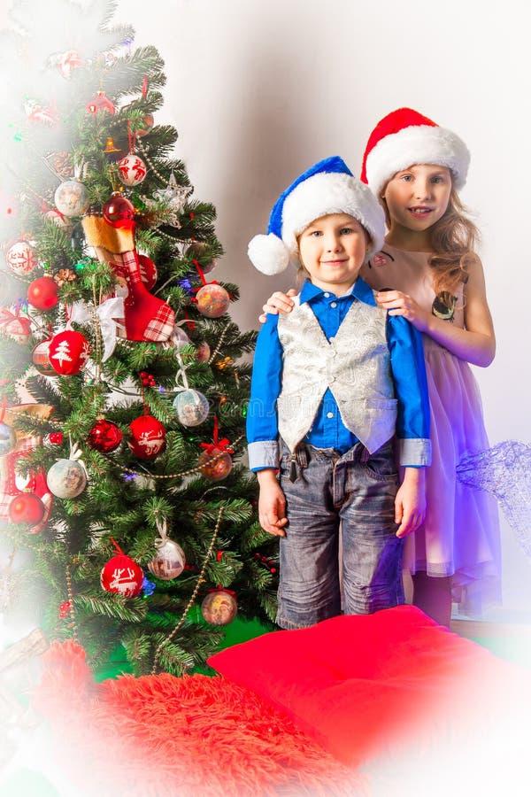 Menino e menina de sorriso no estúdio nas decorações do ano novo fotografia de stock