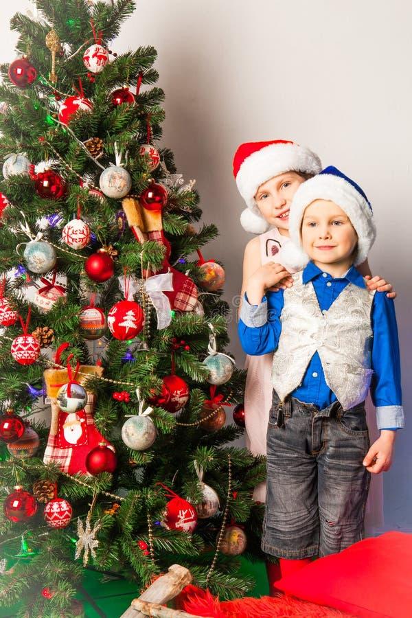 Menino e menina de sorriso no estúdio nas decorações do ano novo fotos de stock