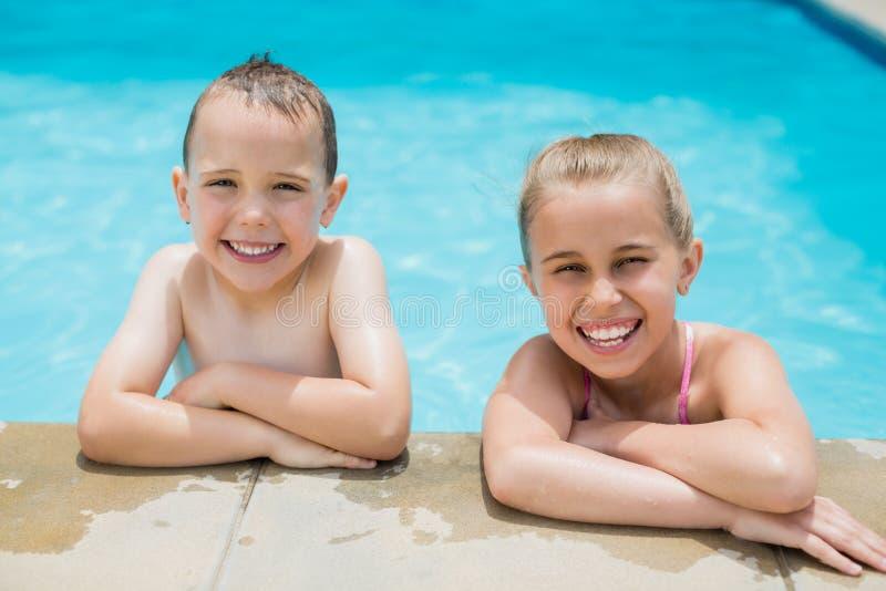 Menino e menina de sorriso que relaxam no lado da piscina imagem de stock