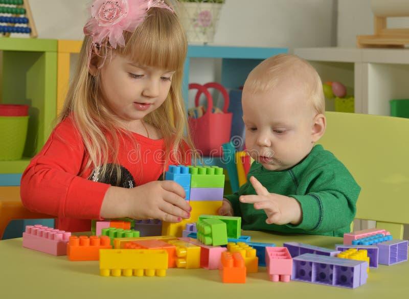 Menino e menina do jogo com cubos fotografia de stock royalty free