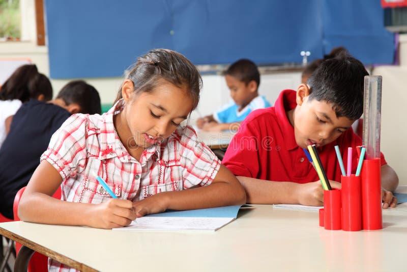 Menino e menina na sala de aula que concentra-se na lição fotografia de stock