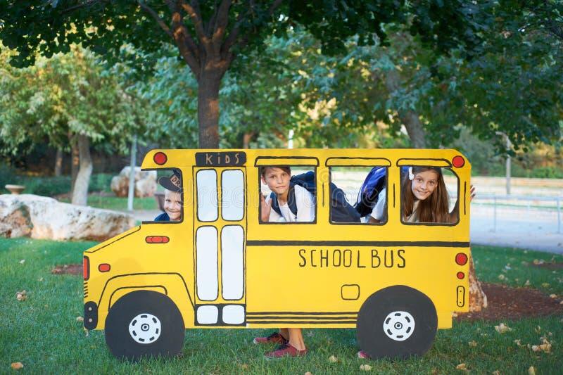 Menino e menina no ônibus escolar pequeno fotografia de stock royalty free