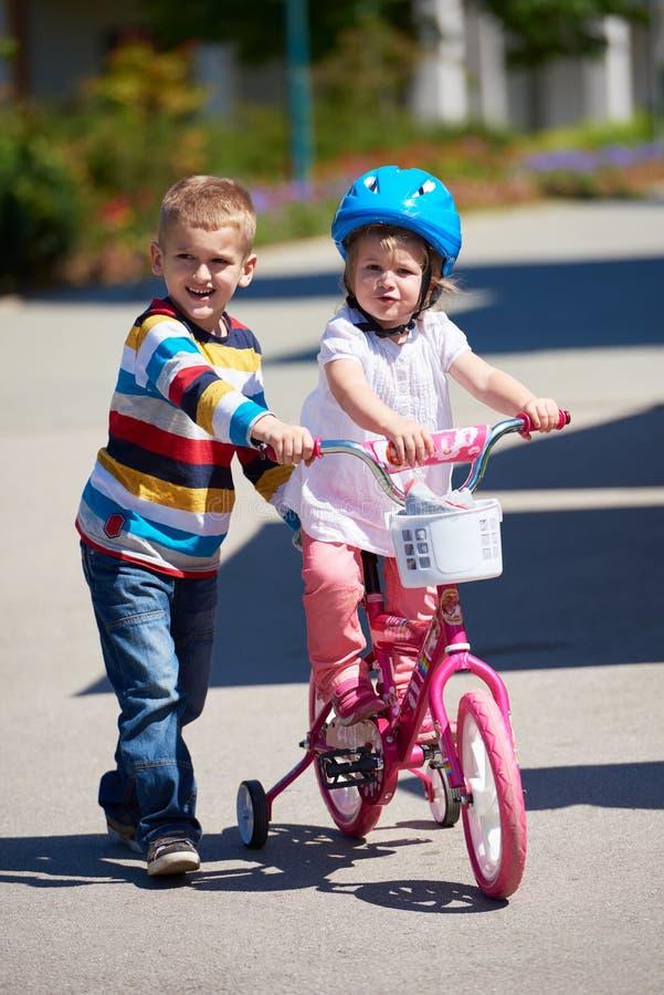 Menino e menina no parque que aprendem montar uma bicicleta fotos de stock