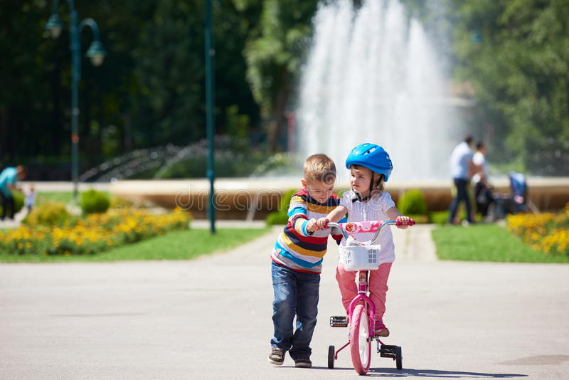 Menino e menina no parque que aprendem montar uma bicicleta imagem de stock