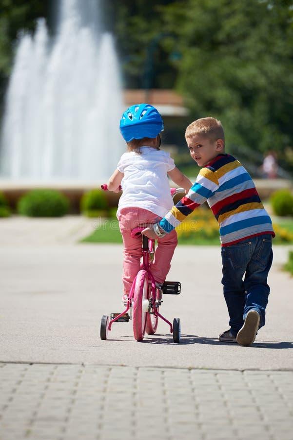 Menino e menina no parque que aprendem montar uma bicicleta foto de stock
