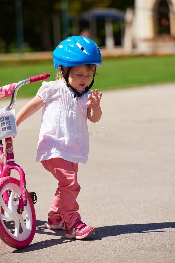 Menino e menina no parque que aprendem montar uma bicicleta foto de stock royalty free
