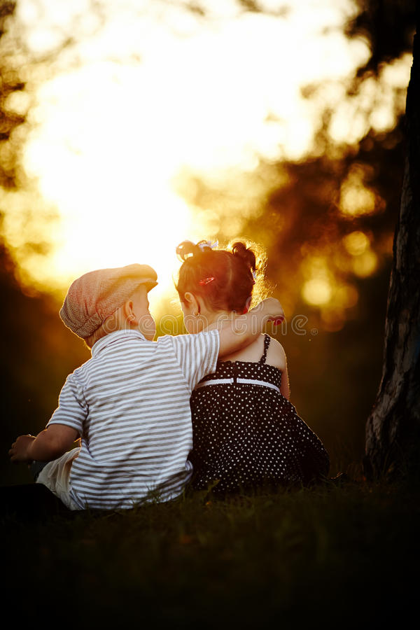 Menino e menina no por do sol fotografia de stock