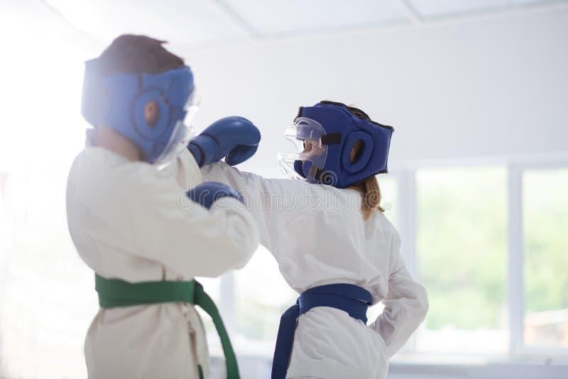 Menino e menina no quimono branco e nos capacetes protetores que têm a luta imagem de stock