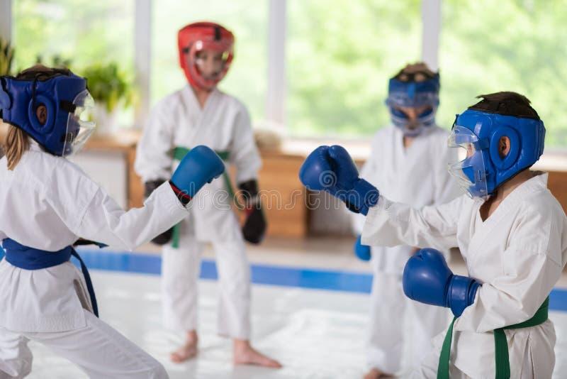 Menino e menina nos capacetes protetores que têm uma luta imagem de stock