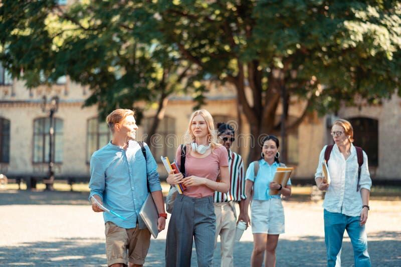 Menino e menina que andam na frente de seus groupmates fotografia de stock royalty free