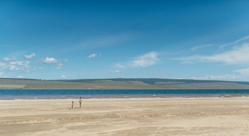 Menino e menina que correm no mar fotografia de stock royalty free