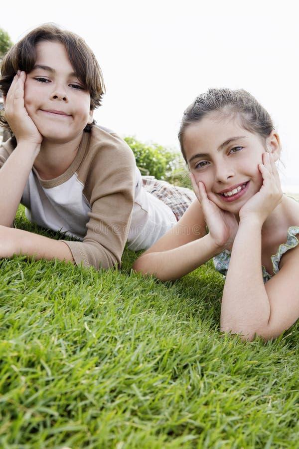 Menino e menina que descansam Chin In Hands While Lying na grama imagens de stock royalty free