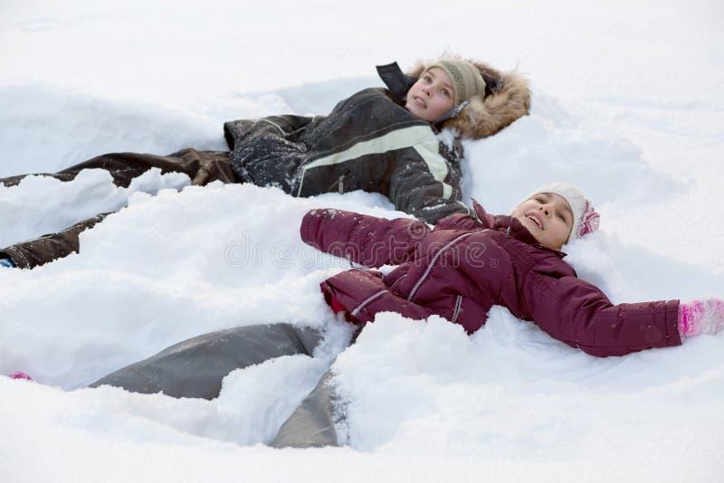 Menino e menina que encontram-se na neve fotos de stock royalty free