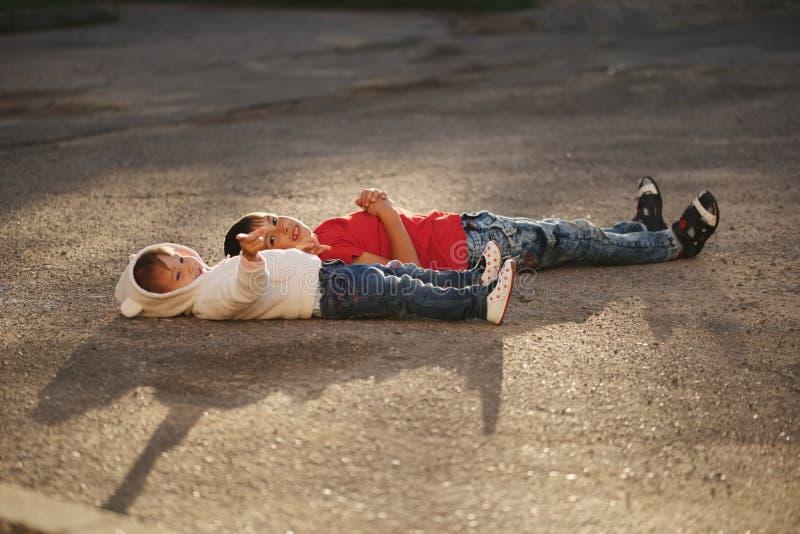 Menino e menina que encontram-se no asfalto fotografia de stock royalty free